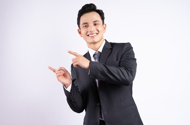 Jeune homme d'affaires asiatique portant costume sur blanc