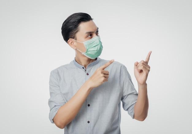 Jeune homme d'affaires asiatique portant un masque hygiénique et pointant vers le haut, prévenir l'infection, 2019-ncov ou coronavirus. maladies respiratoires aéroportées telles que les combats du pm 2,5 et la grippe isolée sur un mur blanc