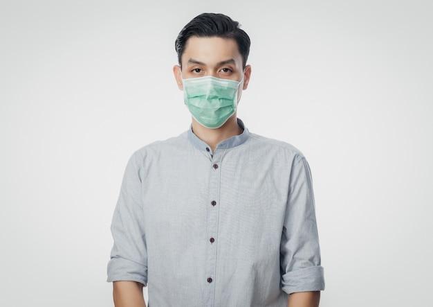 Jeune homme d'affaires asiatique portant un masque hygiénique pour prévenir l'infection, 2019-ncov ou coronavirus. maladies respiratoires aéroportées telles que les combats du pm 2,5 et la grippe isolée sur un mur blanc