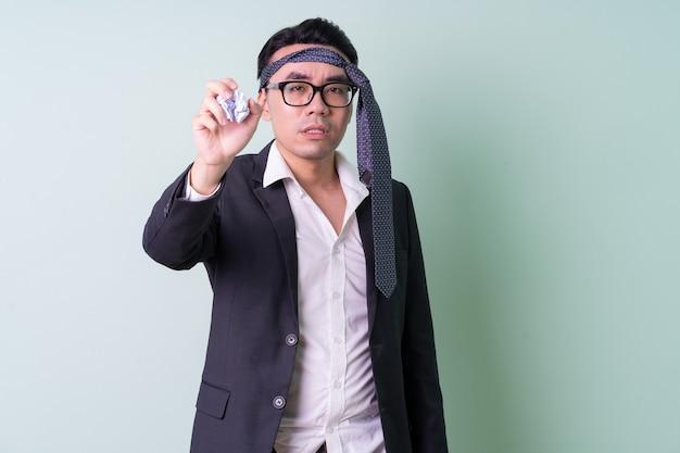 Jeune homme d'affaires asiatique posant sur fond vert
