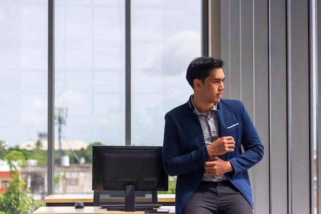 Un jeune homme d'affaires asiatique s'asseoir sur un bureau dans une position confortable. et les mains étaient boutonnées sur les manches