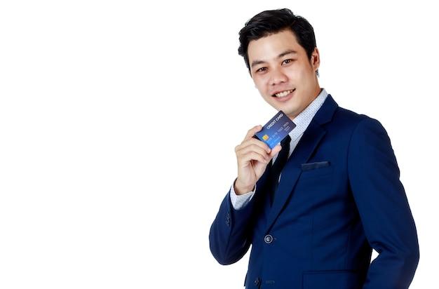 Jeune homme d'affaires asiatique séduisant portant un costume bleu marine avec une chemise blanche et une cravate souriant et tenant sa carte de crédit bleue sur fond blanc. isolé