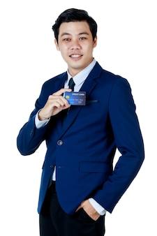 Jeune homme d'affaires asiatique séduisant portant un costume bleu marine avec une chemise blanche et une cravate souriant et tenant sa carte de crédit bleue et une main dans sa poche sur fond blanc. isolé