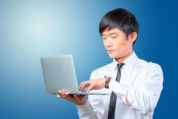 Jeune homme d'affaires asiatique souriant tenant un ordinateur portable