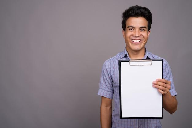 Jeune homme d'affaires asiatique tenant le presse-papiers contre le mur gris