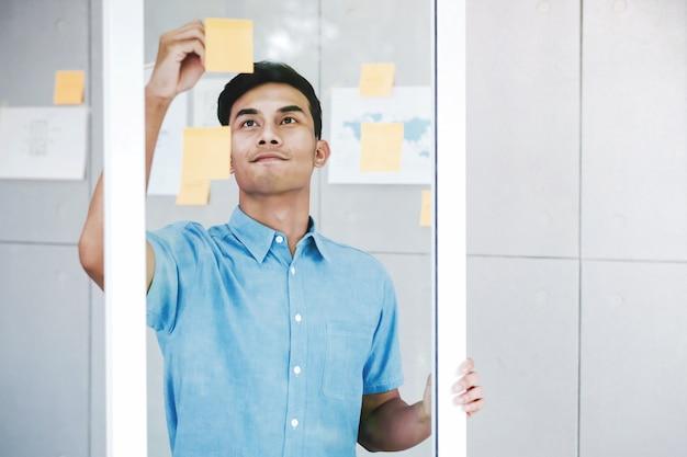 Jeune homme d'affaires asiatique travaillant dans la salle de réunion de bureau.