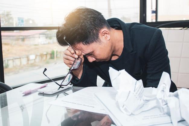 Jeune homme d'affaires asiatique travaille sur la pression dans le bureau lumineux.