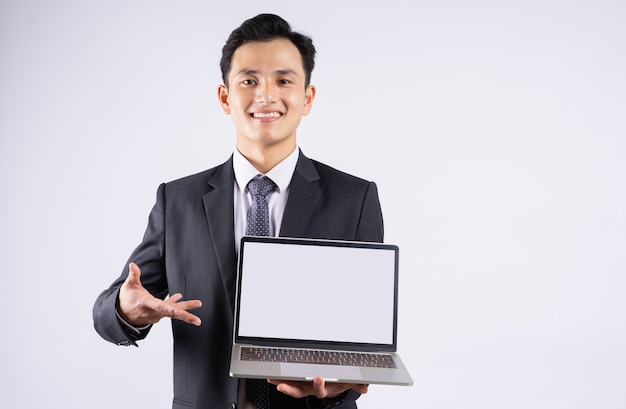 Jeune homme d'affaires asiatique utilisant un ordinateur portable sur blanc