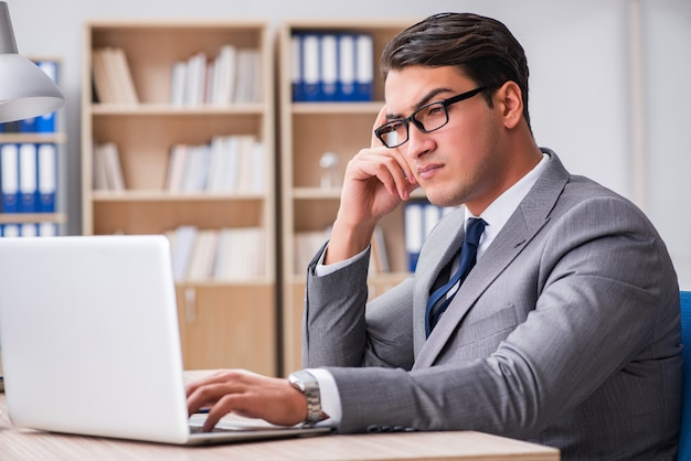 Jeune homme d'affaires assis au bureau