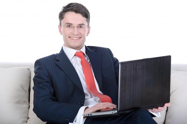 Jeune homme d'affaires assis sur un canapé.