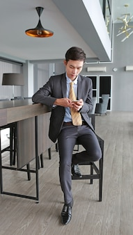 Jeune homme d'affaires assis à la chaise sur le lieu de travail au bureau en utilisant le smartphone