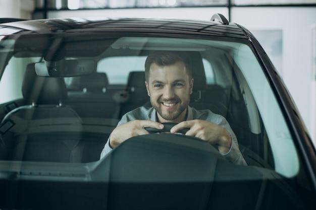 Jeune homme d'affaires assis dans une voiture