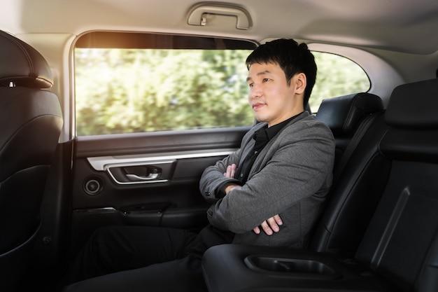 Jeune homme d'affaires assis sur le siège arrière de la voiture