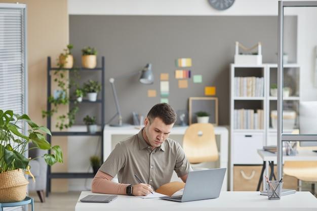 Jeune homme d'affaires assis à la table devant l'ordinateur portable et rédiger des plans dans son bloc-notes, il travaille au bureau