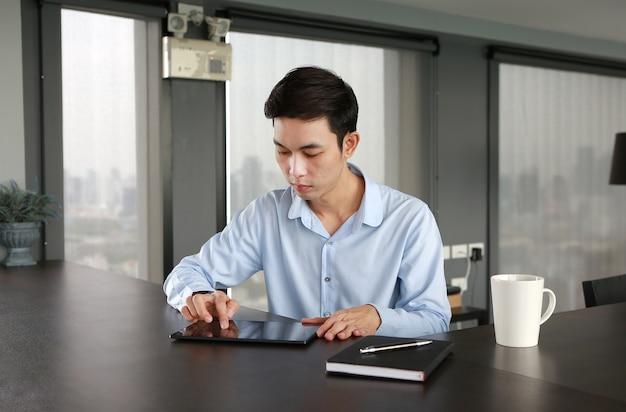 Jeune homme d'affaires assis à la table sur le lieu de travail au bureau à l'aide de la tablette