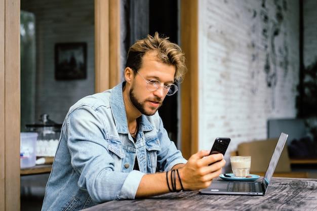 Jeune homme d'affaires attrayant dans un café travaille pour un ordinateur portable, boit du café.