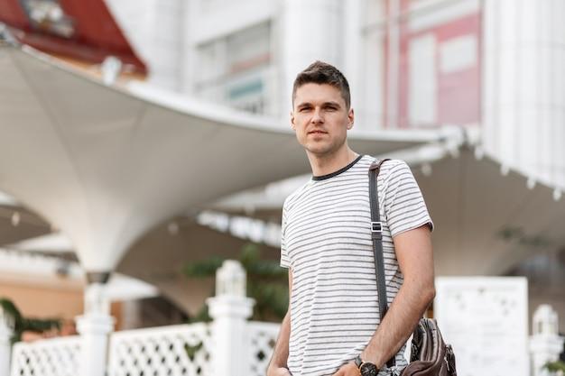 Jeune homme d'affaires attrayant dans un t-shirt rayé à la mode avec un sac vintage en cuir posant dans la ville.
