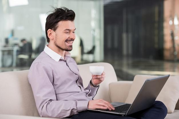 Jeune homme d'affaires attrayant est assis sur le canapé.
