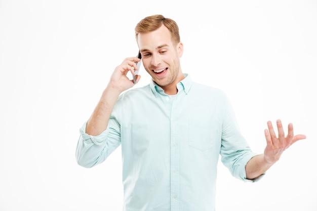 Jeune homme d'affaires attrayant et gai debout et parlant au téléphone portable sur un mur blanc