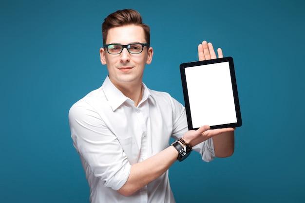 Jeune homme d'affaires attrayant en montre coûteuse, lunettes noires et chemise blanche tenir comprimé vide
