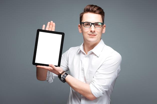 Jeune homme d'affaires attrayant en montre coûteuse, lunettes noires et chemise blanche tenir tablette vide