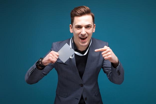 Jeune homme d'affaires attrayant en veste grise, montre coûteuse, chemise noire