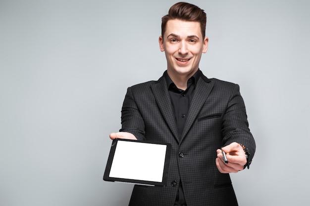 Jeune homme d'affaires attrayant en veste noire, montre coûteuse et chemise noire tenir tablette vide
