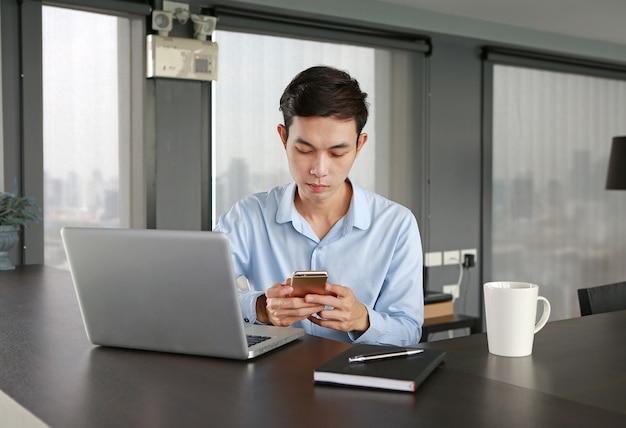 Jeune homme d'affaires au lieu de travail au bureau en utilisant le smartphone