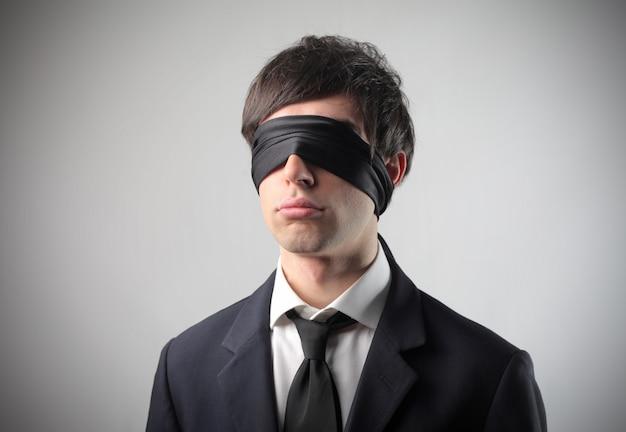 Jeune homme d'affaires aux yeux bandés