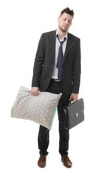 Jeune homme d'affaires aux yeux fermés tenant un oreiller et une mallette, isolé sur blanc