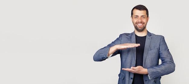 Jeune homme d'affaires avec une barbe dans une veste, faisant des gestes avec ses mains montrant un signe de grande et grande taille un symbole de mesure.