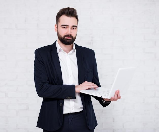 Jeune homme d'affaires barbu à l'aide d'un ordinateur sur fond de mur de briques blanches