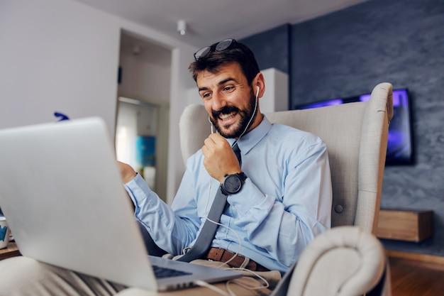 Jeune homme d'affaires barbu attrayant souriant assis dans une chaise à la maison et ayant une conférence téléphonique sur un ordinateur portable.