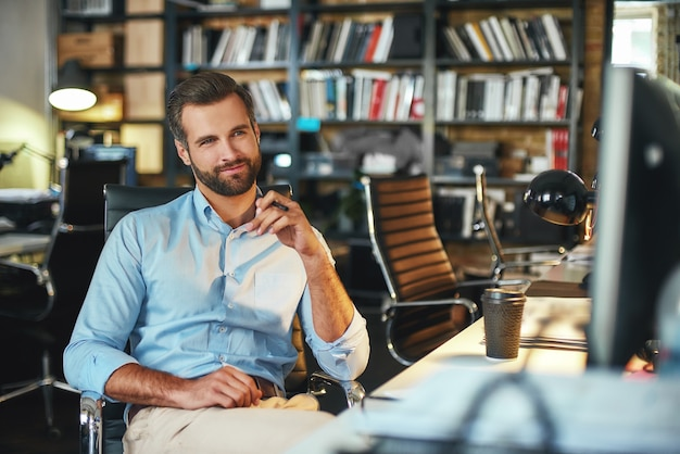 Jeune homme d'affaires barbu confiant et intelligent en tenue de soirée pensant à quelque chose et souriant