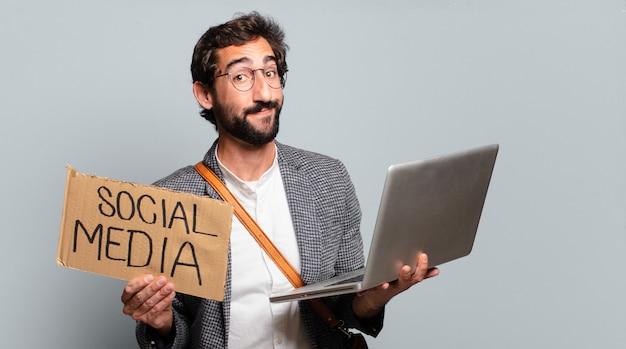 Jeune homme d'affaires barbu et fou avec un ordinateur portable