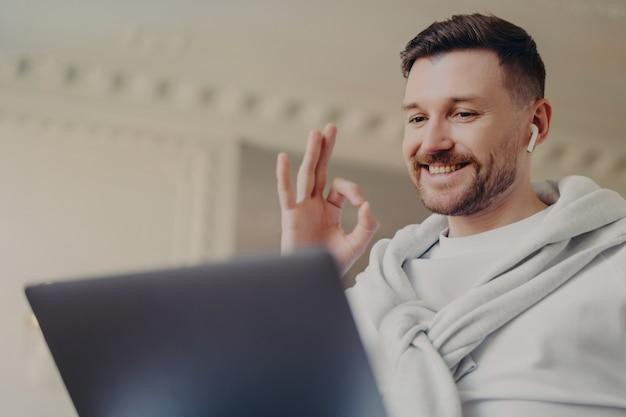 Jeune homme d'affaires barbu positif montrant sa vie réussie par geste ok tout en ayant une vidéoconférence avec son patron ou ses collègues sur un ordinateur portable. indépendant masculin dans des écouteurs travaillant à distance de la maison