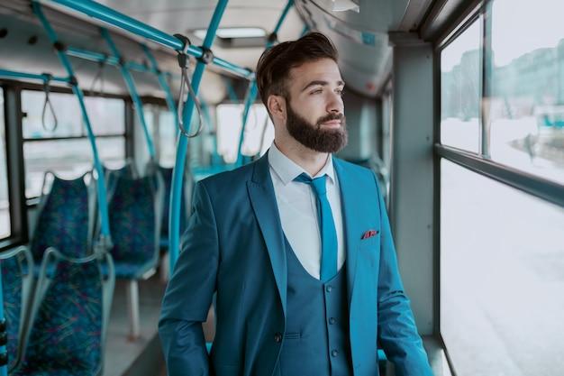Jeune homme d'affaires barbu réfléchi en costume bleu, debout dans les transports publics et à la recherche de la fenêtre de l'auge.