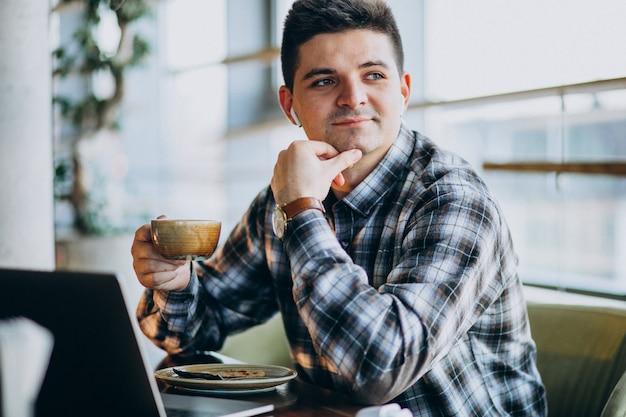 Jeune homme d'affaires beau à l'aide d'un ordinateur portable dans un café