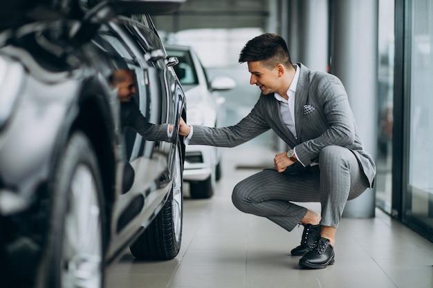 Jeune homme d'affaires beau choisir une voiture dans une salle d'exposition