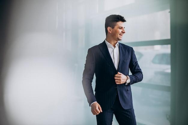 Jeune homme d'affaires beau dans un costume dans un bureau