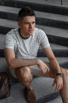 Jeune homme d'affaires beau dans des vêtements à la mode dans d'élégantes chaussures marron en daim avec un sac vintage en cuir au repos après le travail