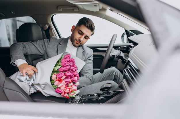 Jeune homme d'affaires beau livrer le bouquet de belles fleurs