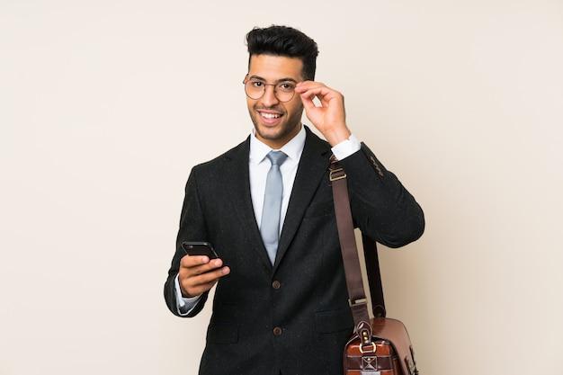 Jeune homme d'affaires beau sur mur isolé