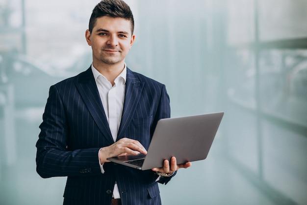 Jeune homme d'affaires beau avec ordinateur portable au bureau