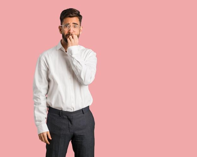 Jeune homme d'affaires beau se ronger les ongles, nerveux et très inquiet