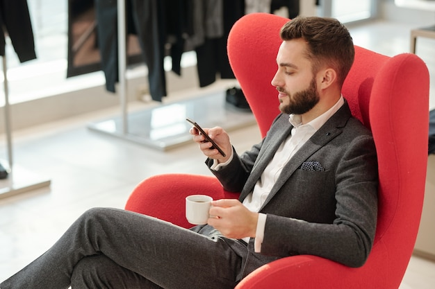 Jeune homme d'affaires bien habillé avec une tasse de thé textos dans smartphone alors qu'il était assis dans un fauteuil confortable rouge en boutique