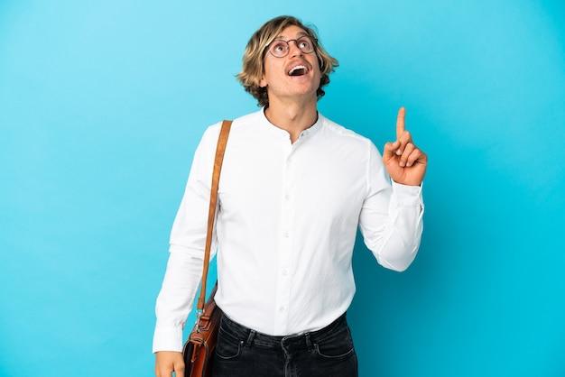 Jeune homme d'affaires blond isolé pointant vers le haut et surpris
