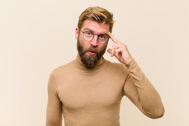 Jeune homme d'affaires blond à la recherche de surprise, bouche bée, choqué, réalisant une nouvelle pensée, idée ou concept
