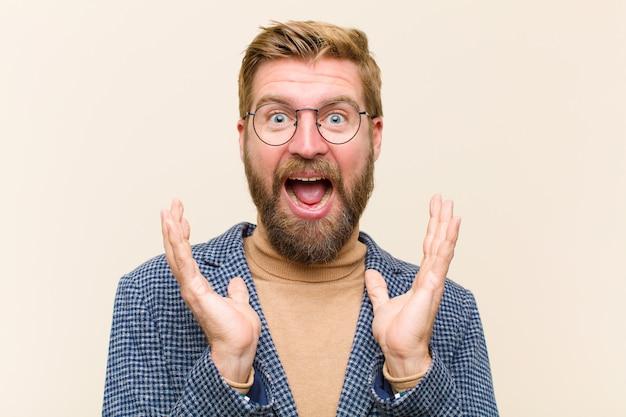 Jeune Homme D'affaires Blond Se Sentant Choqué Et Excité, Riant, émerveillé Et Heureux D'une Surprise Inattendue Photo Premium