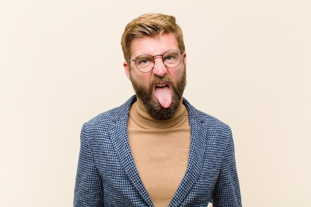 Jeune homme d'affaires blond se sentant dégoûté et irrité, tire la langue, n'aimant pas quelque chose de méchant et dégueulasse